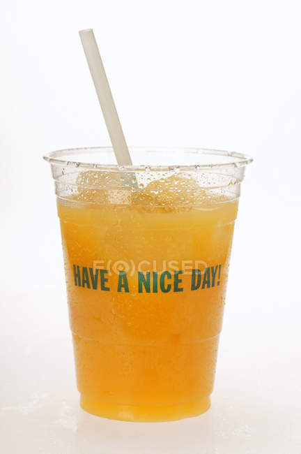 Orange juice in plastic tumbler — Stock Photo