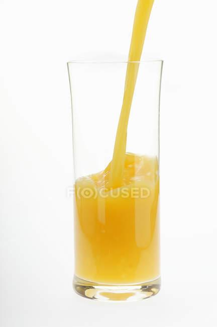 Orangensaft Gießen in Glas — Stockfoto