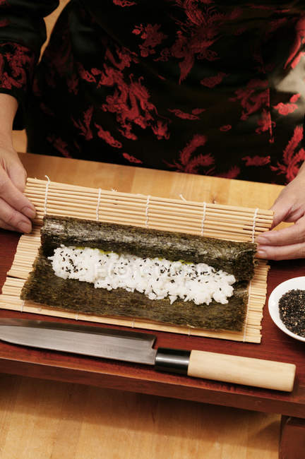Frau rollt Reis in Nori-Laken — Stockfoto