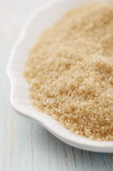 Closeup vista marrom do açúcar de cana em prato branco — Fotografia de Stock