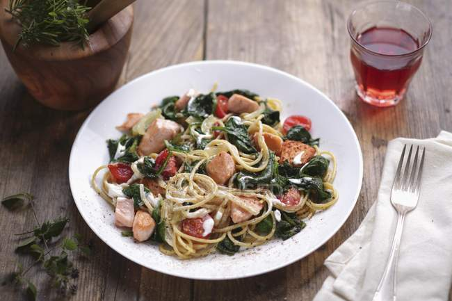 Spaghetti with salmon and spinach — Stock Photo