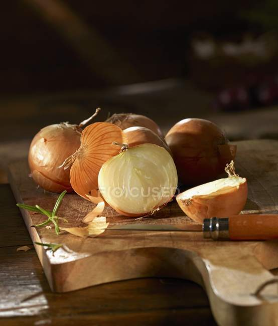 Onions on a wooden chopping board — Stock Photo