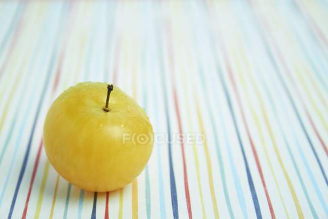 Yellow plum on coloured tablecloth — Stock Photo