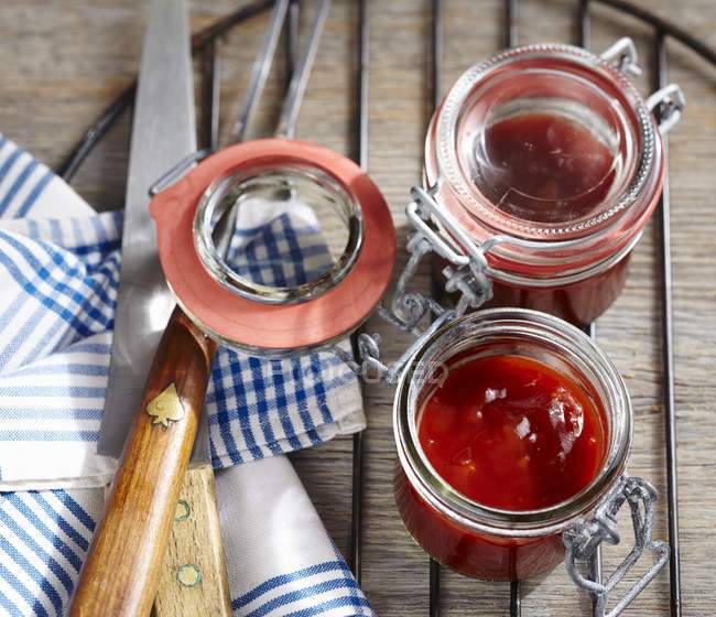Homemade barbecue sauce in preserving jars over wooden surface — Stock Photo