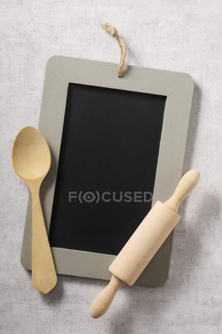 Vista superior de una pizarra, una cuchara de madera y un rodillo - foto de stock