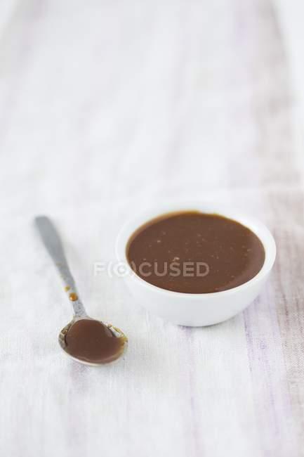 Vista de cerca de salsa de caramelo en un tazón y cuchara - foto de stock