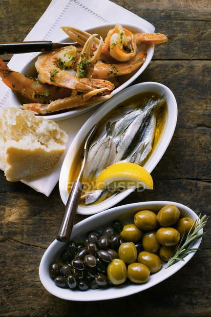 Мариновані сардини, смажені креветки і оливки у стравах над деревної поверхні — стокове фото