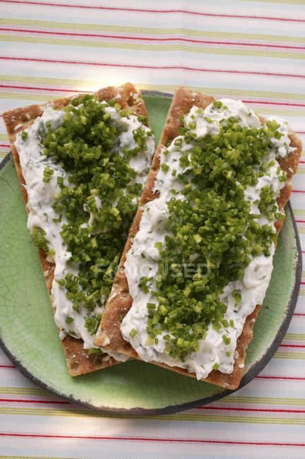 Getreidescheiben mit Quark und Schnittlauch auf grüne Platte über Tisch — Stockfoto