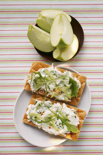 Getreidescheiben mit Quark und Rucola; frische Apfelspalten auf weißen Teller und auf schwarze — Stockfoto