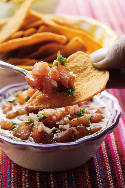 Closeup view of putting tomato Salsa on tortilla chip — Stock Photo