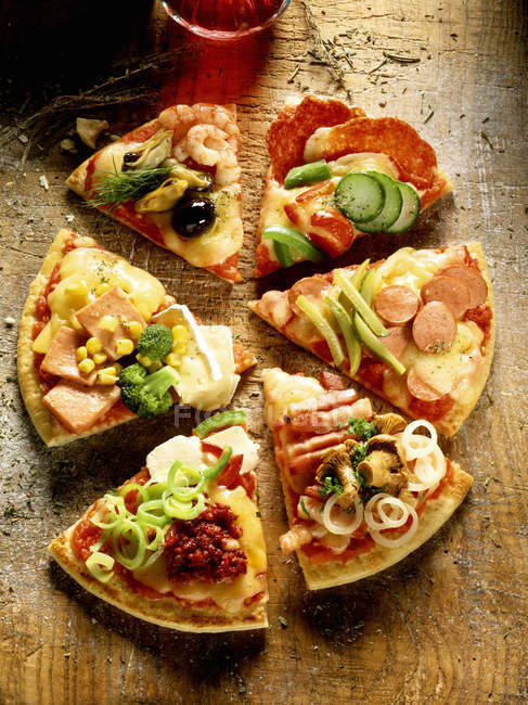 Pedazos de pizza con ingredientes diferentes - foto de stock