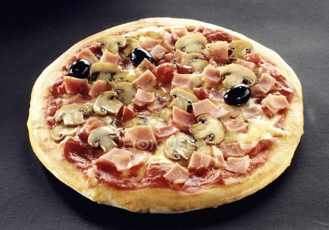 Піца з шинкою, грибами та оливками — стокове фото