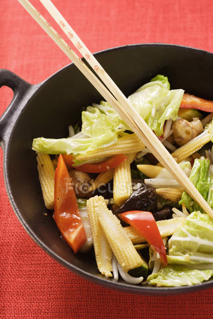 Ингредиенты для азиатских овощное блюдо в воке красный поверхности — стоковое фото