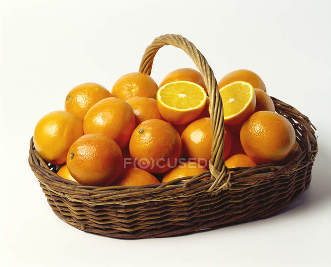 Апельсины в мелкой плетеной корзине — стоковое фото
