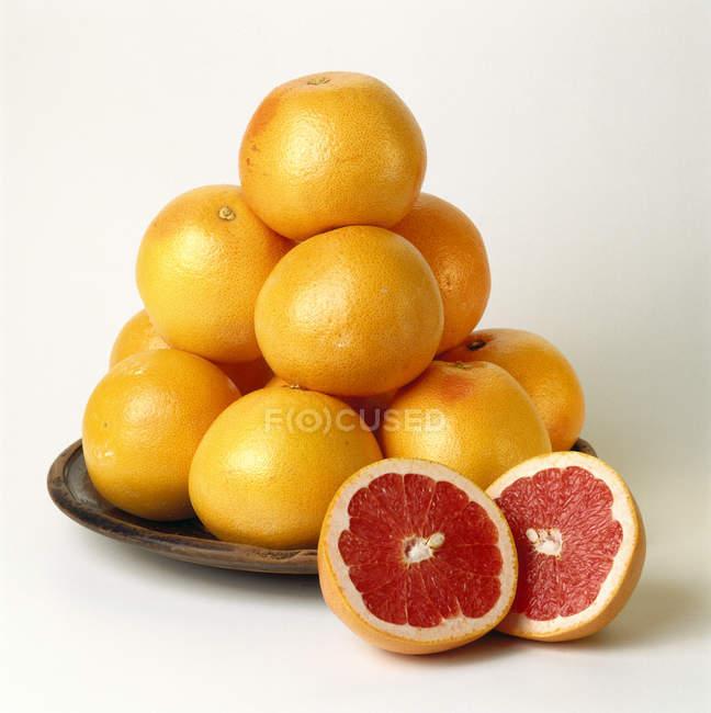 Розовые грейпфруты на плите — стоковое фото