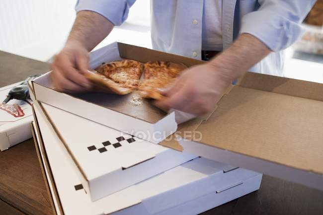 L'homme prend un morceau de pizza — Photo de stock