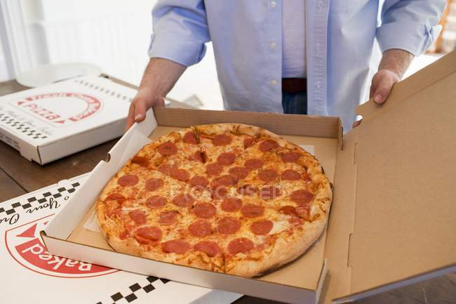 Mann hält Pizza-Box — Stockfoto