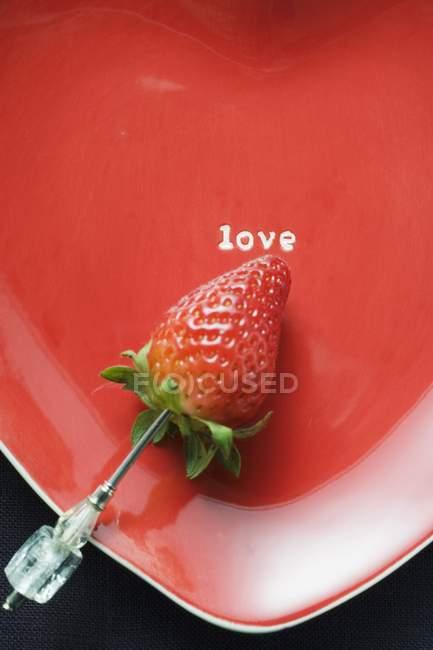 Клубника на красной пластинке в форме сердца — стоковое фото