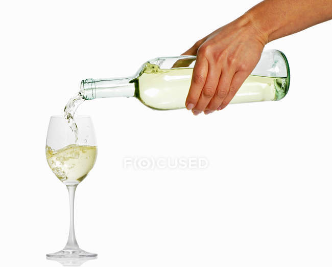 Female hand pouring white wine — Stock Photo
