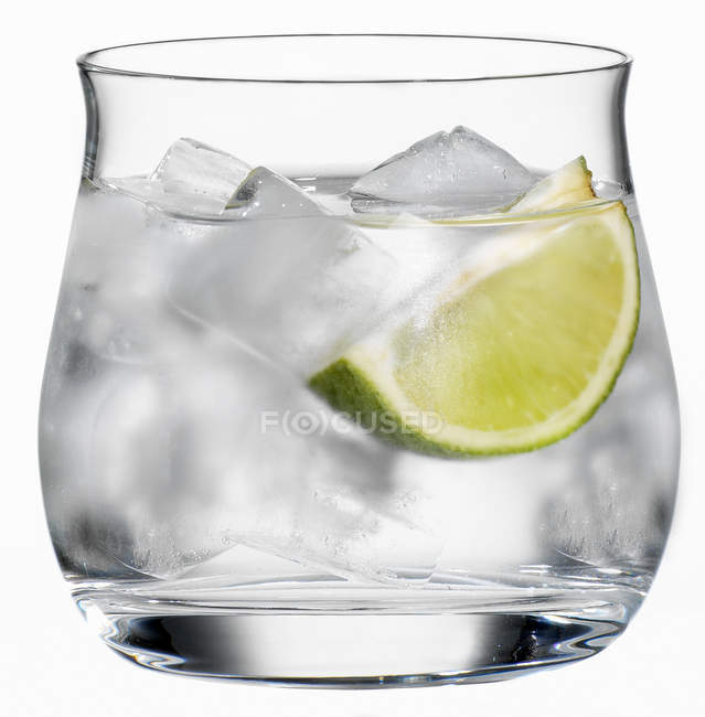Glass of water with lime slice — Stock Photo