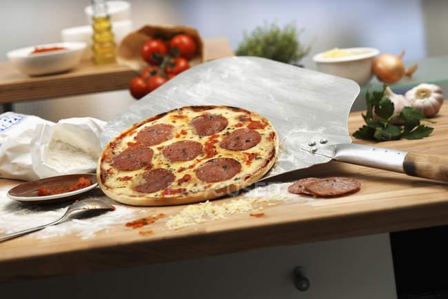 Salami-Pizza mit Pizzapaddel — Stockfoto