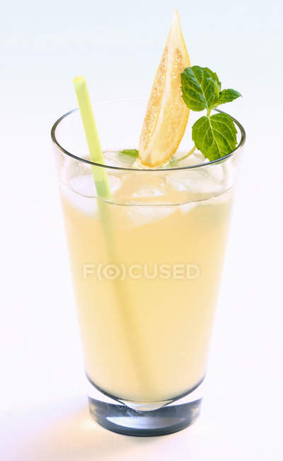 Iced White Lady cocktail with fruit wedge, straw and leaves — Stock Photo