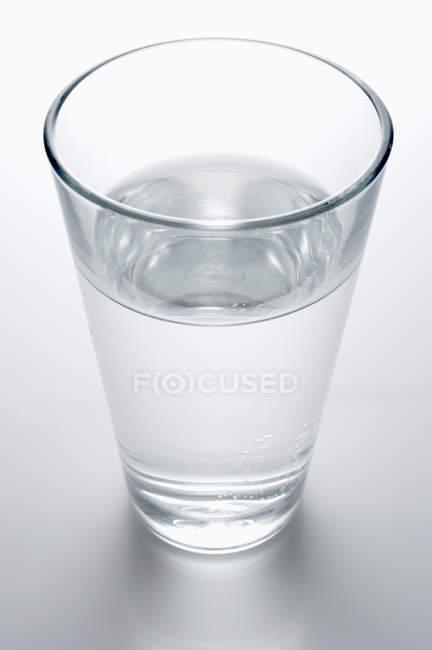 Стакан води на сірому таблиці — стокове фото