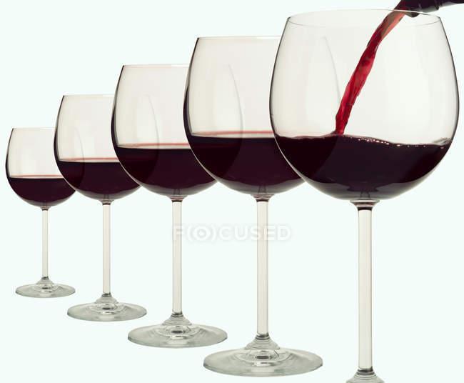 Cinco copas de vino tinto - foto de stock
