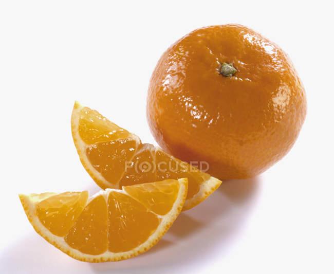 Fresh orange with wedges — Stock Photo