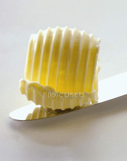 Primo piano vista di un ricciolo di burro su una lama di coltello — Foto stock