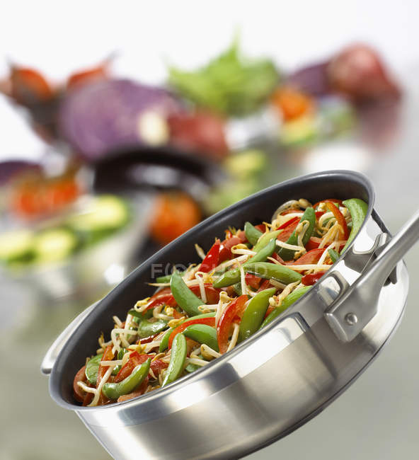 Stir-fried vegetables in frying pan on blurred background — Stock Photo