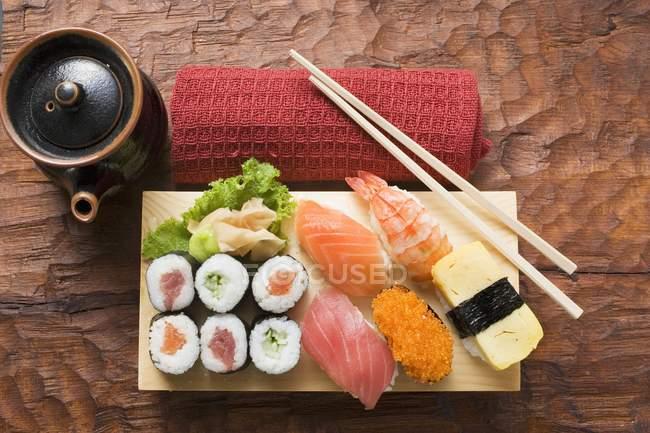 Assorted sushi on sushi board — Stock Photo
