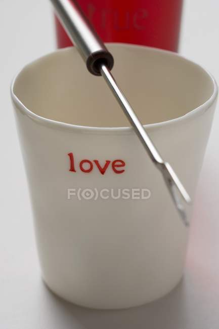 Closeup view of beaker with the word love and fondue fork — Stock Photo