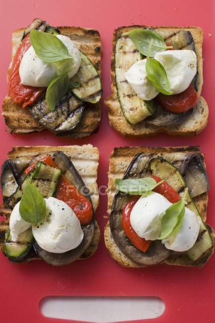 Vegetables and mozzarella on slices of grilled bread on red chopping board — Stock Photo