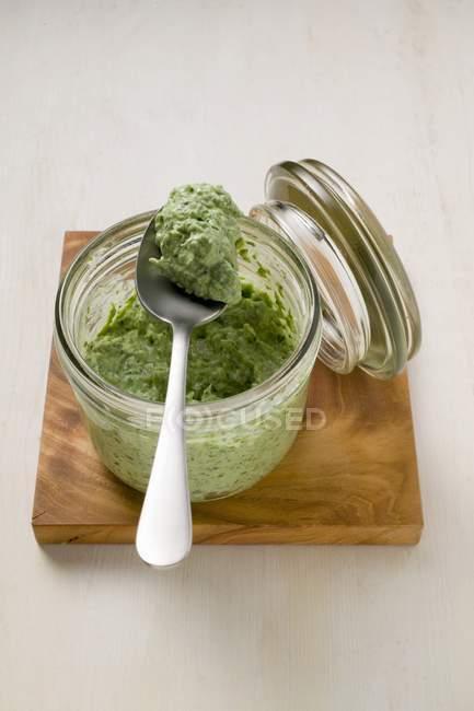 Vista del primo piano del pesto di insalata di mais in barattolo di vetro e il cucchiaio — Foto stock