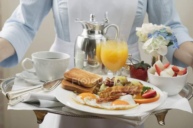 Cropped view of chambermaid carrying breakfast tray — Stock Photo