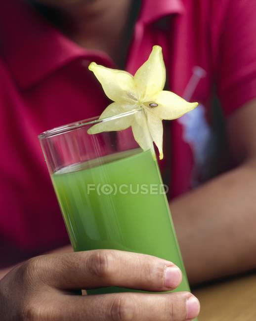 Uomo che tiene il succo di frutta kiwi — Foto stock