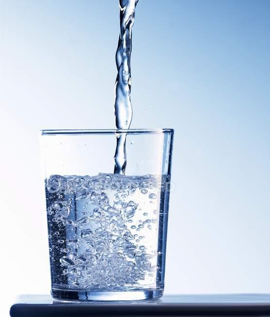 Derramando água em vidro — Fotografia de Stock