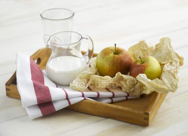 Vista de cerca de manzanas y leche en bandeja - foto de stock