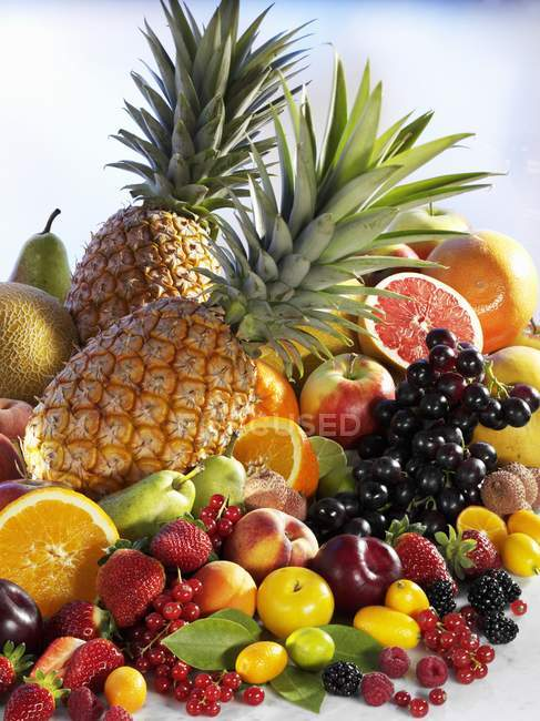 Pineapples with heap of fresh fruits and berries — Stock Photo