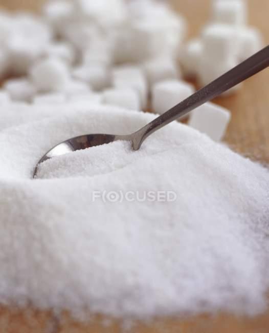 Açúcar granulado e cubos de açúcar com colher — Fotografia de Stock
