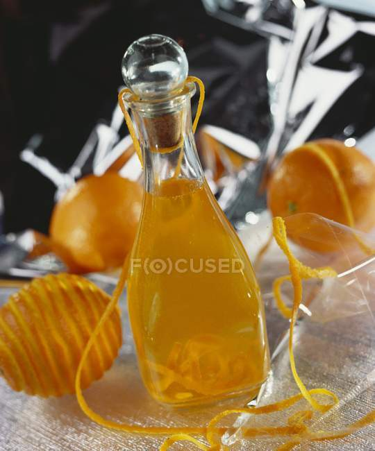 Closeup view of homemade orange liqueur in glass bottle — Stock Photo