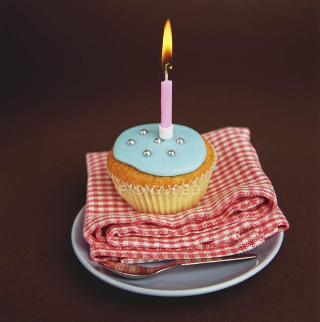 Cupcake with blue icing and candle — Stock Photo