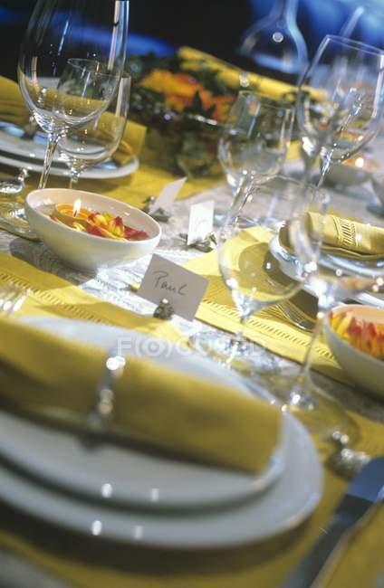 Vista inclinada de puesto mesa decorada con velas encendidas y etiquetas - foto de stock