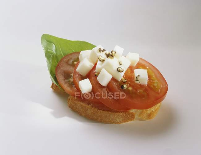 Canap: tomato, mozzarella and basil on slice of baguette on white background — Stock Photo
