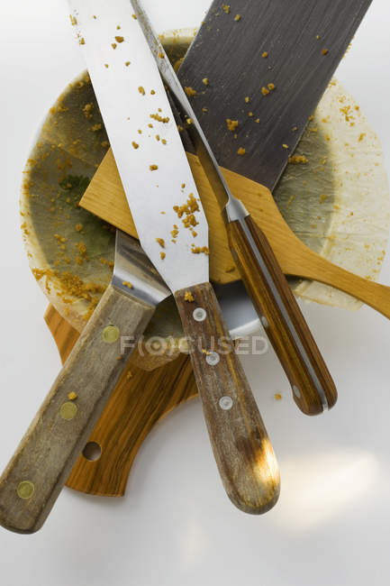 Top view of various serving implements and baking dish on chopping board — Stock Photo