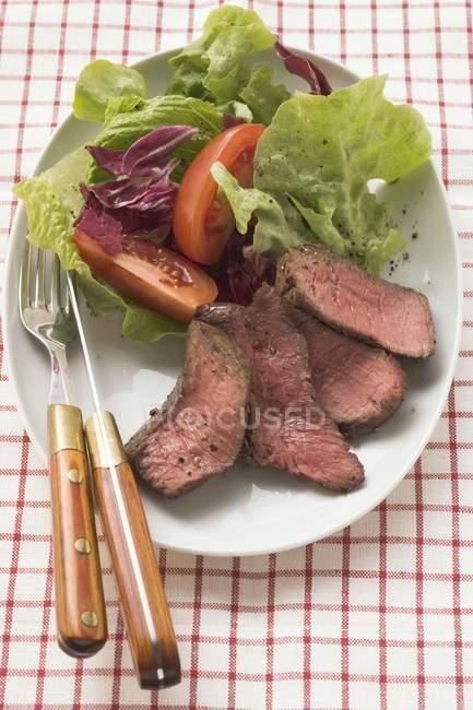 Нарізаний стейк яловичина з салатом — стокове фото