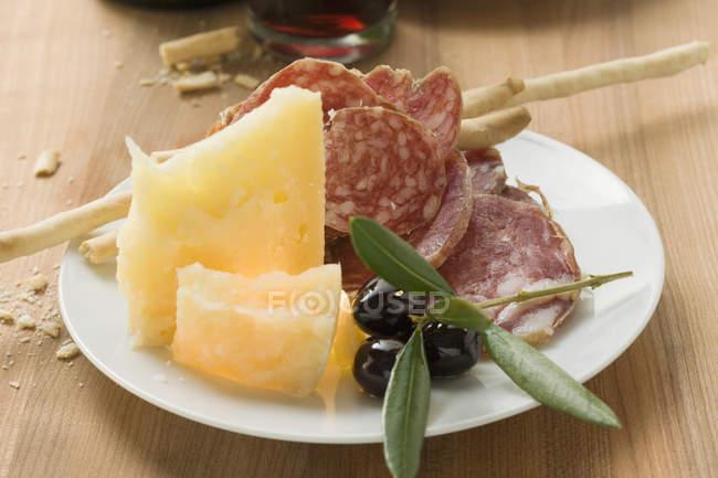 Салями с сыром и grissini на плите — стоковое фото