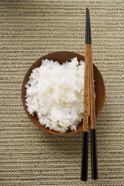 Bowl of rice and chopsticks — Stock Photo