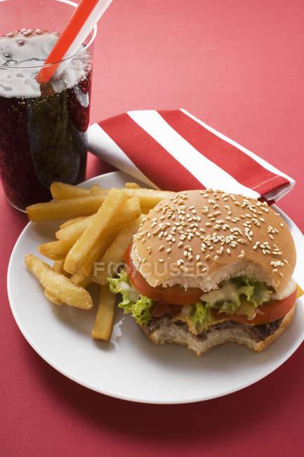 Bitten Cheeseburger with chips — Stock Photo